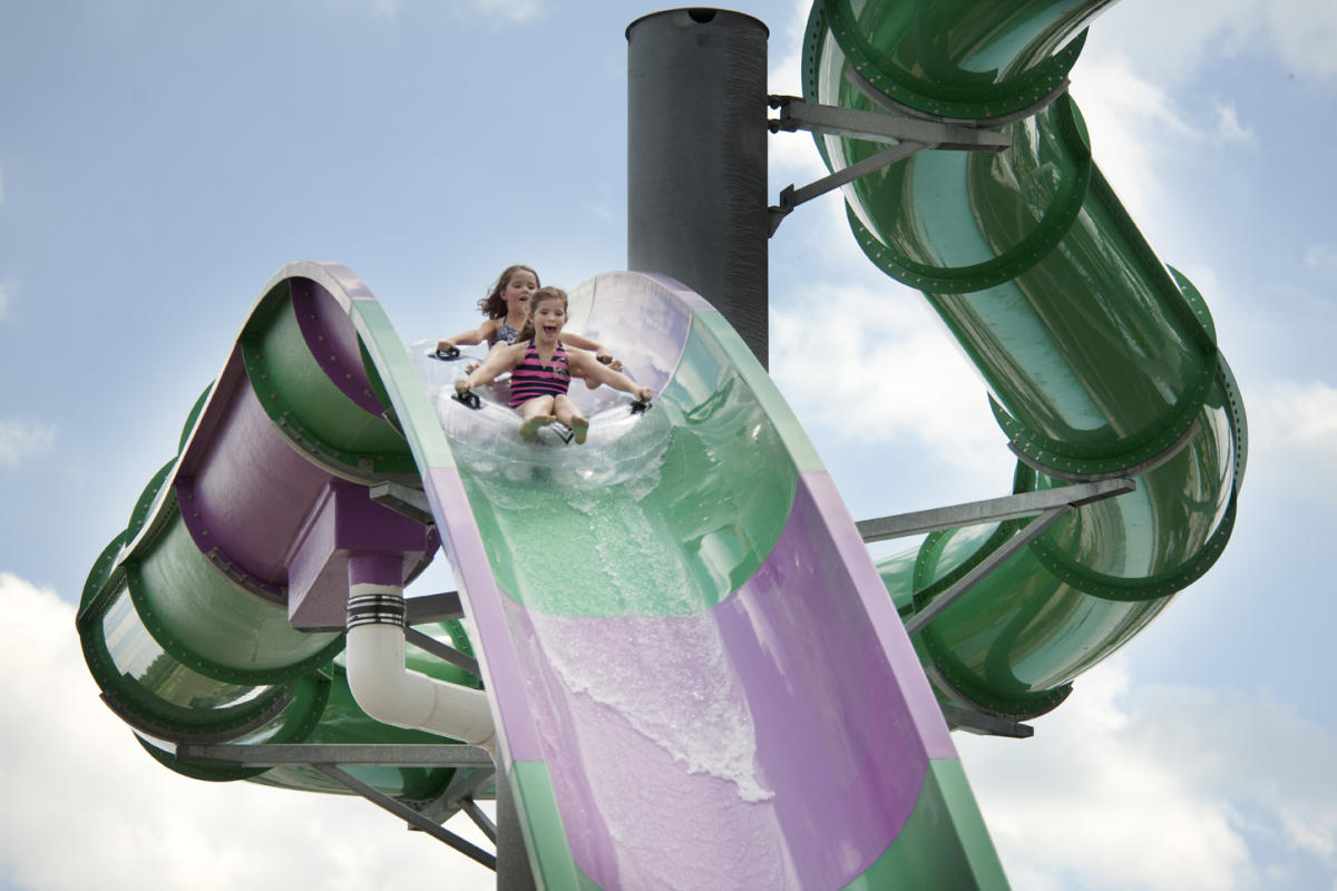 Two young girls tubing down slide at Zoombezi Bay.