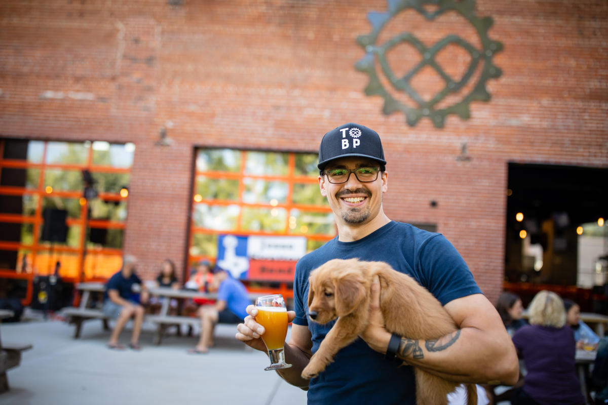 Owner holding his dog and a beer at the Brewing Projekt