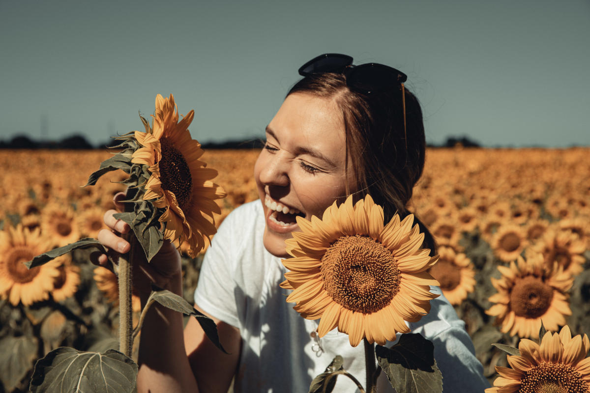 Laughing in a field of sunflowers at Babbette's Seeds of Hope