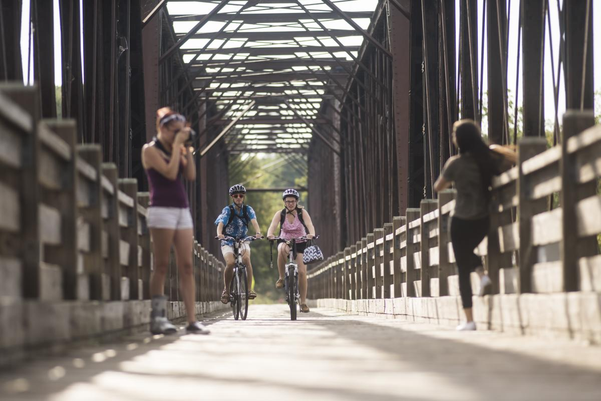Bikers on the Phoenix Park pedestrian bridge in downtown Eau Claire