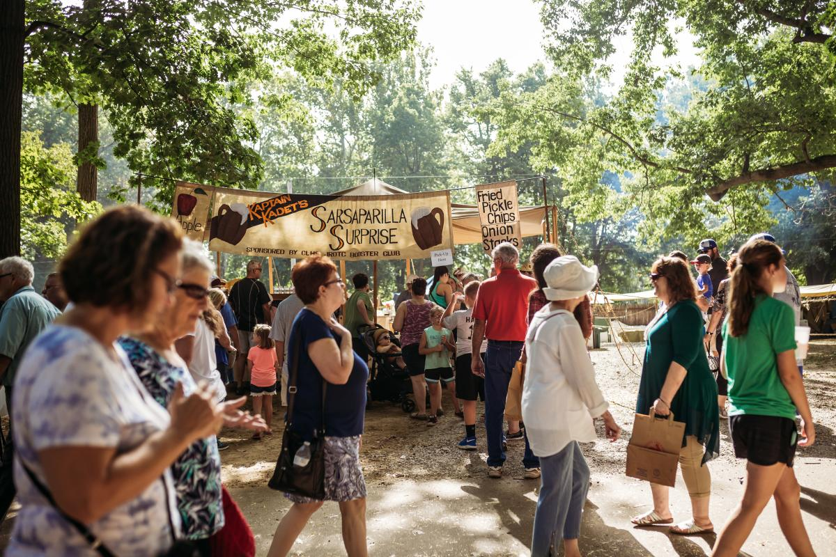 Individuals walking past a food vendor at the Johnny Appleseed Festival - a period authentic festival in Fort Wayne, Indiana.