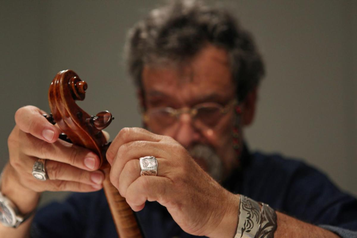 Violinmaker Amnon Weinstein adjusts the strings on one of the Violins of Hope