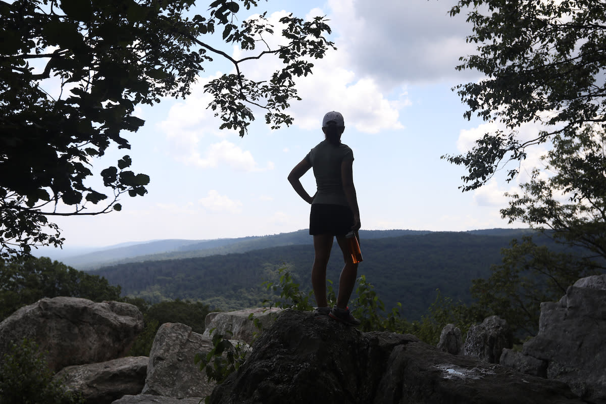 Hiker standing on the top of a rock overlooking Catoctin Mountain Park