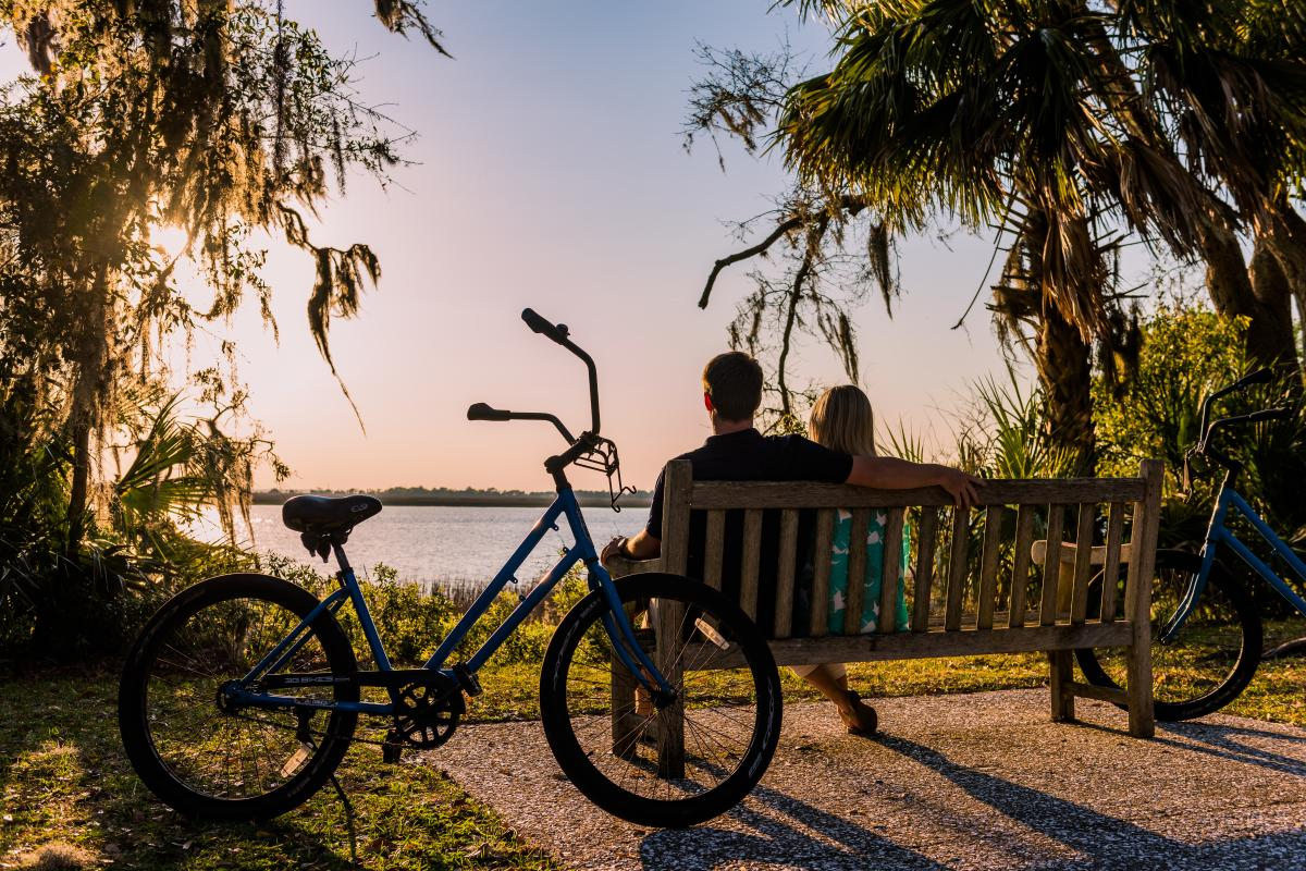 A couple takes a break from their bike ride to enjoy the sunset along the bike trail on Jekyll Island, Georgia