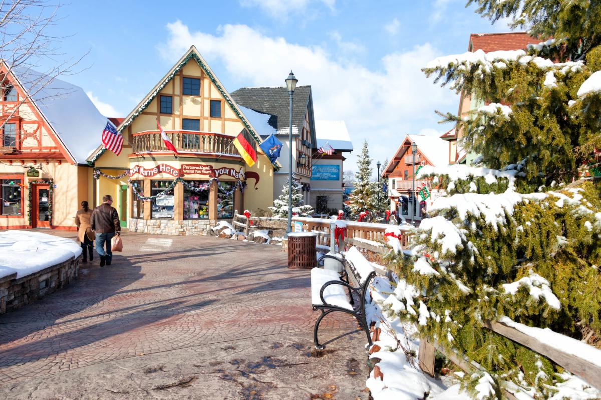 A couple walk through snow covered Frankenmuth River Place shops