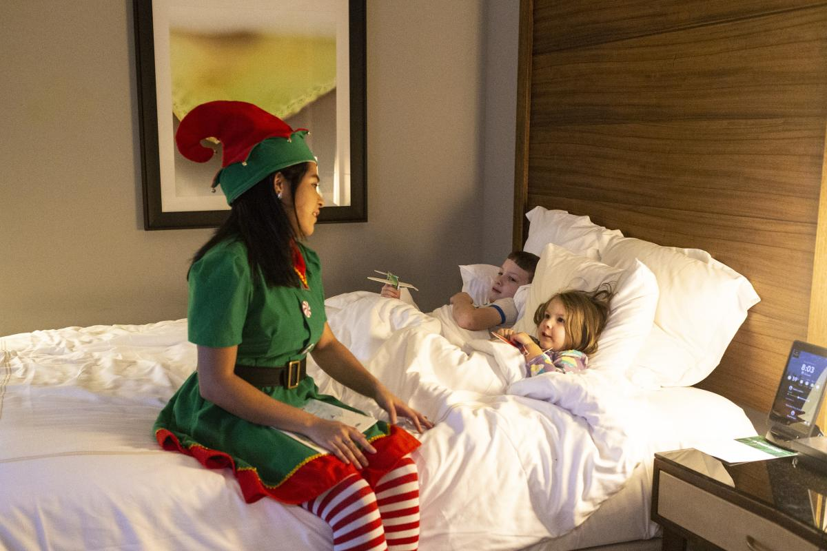 An Elf Hostess tucks children in at The Woodlands Resort