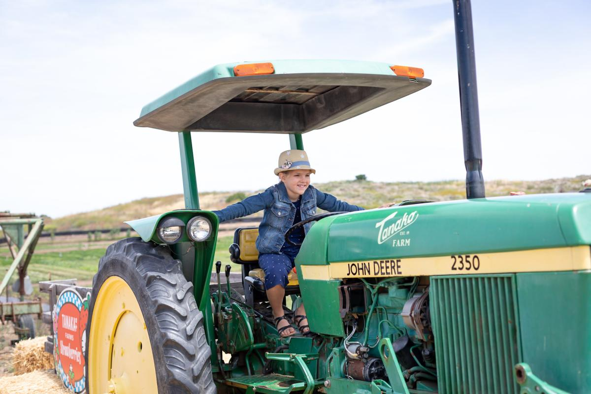 Girl riding a green John Deere tractor at Tanaka Farms