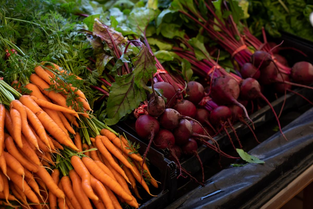 Bunches of carrots and beets at a produce stand