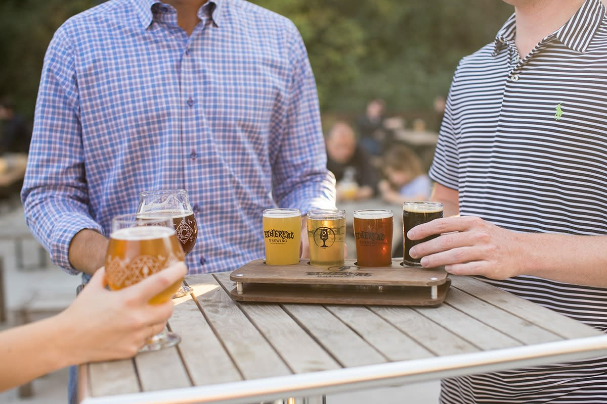 Three people enjoy a flight of beers from Ethereal Brewing.