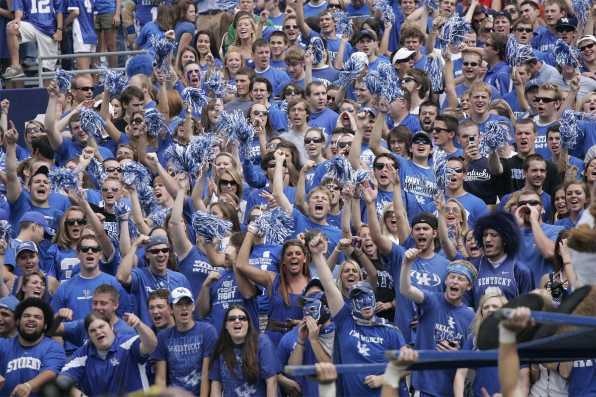 A huge crowd of excited fans all wearing University of Kentucky blue t-shirts cheers and waves blue and silver pom poms in the air.