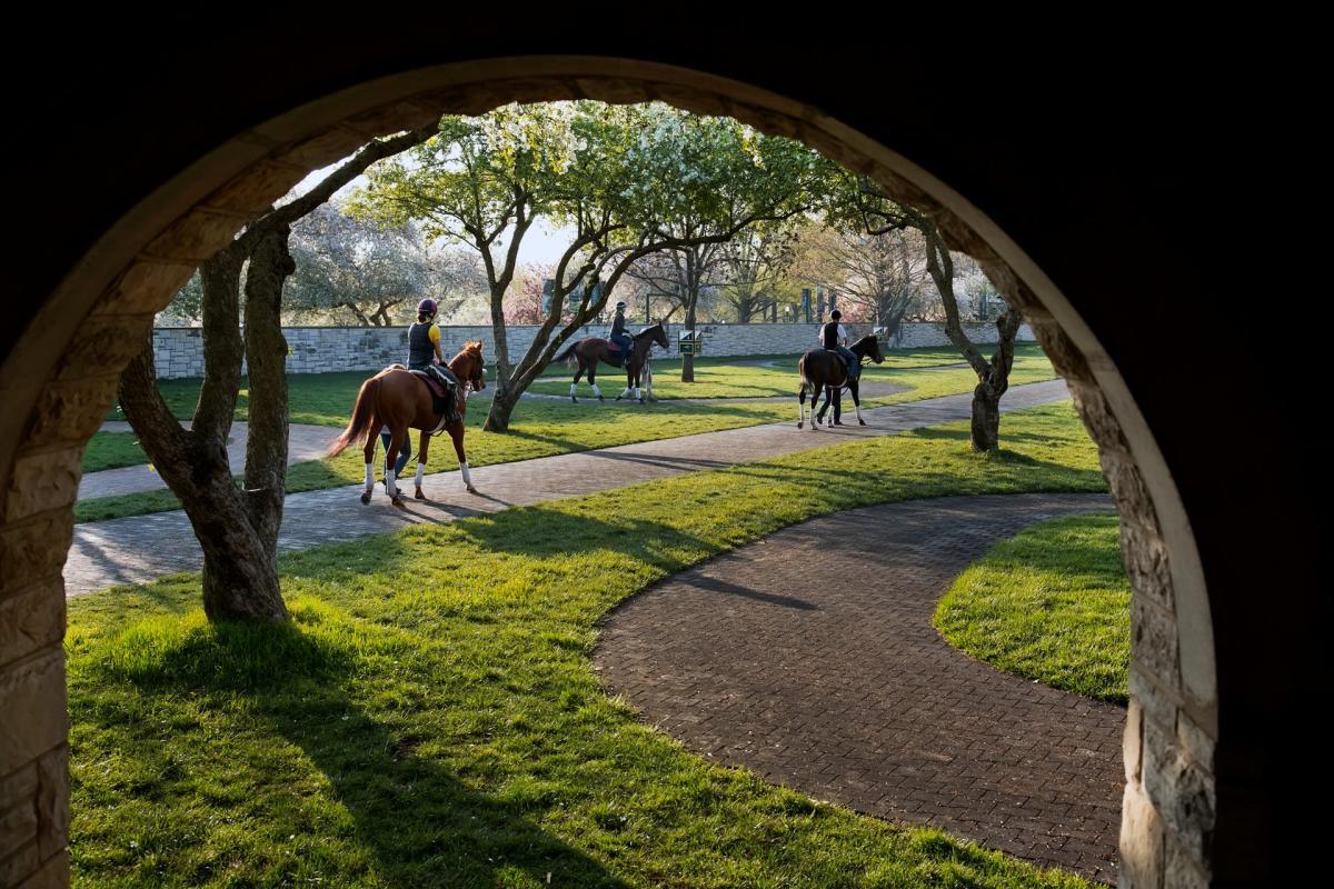 Jockeys ride their horses through curving brick pathways at Keeneland.