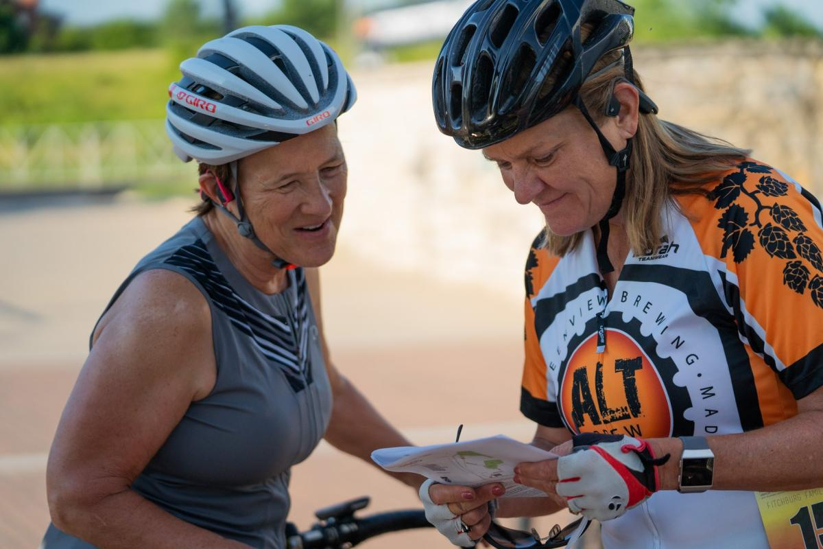 Two women with bicycle helmets on looking at a map and smiling