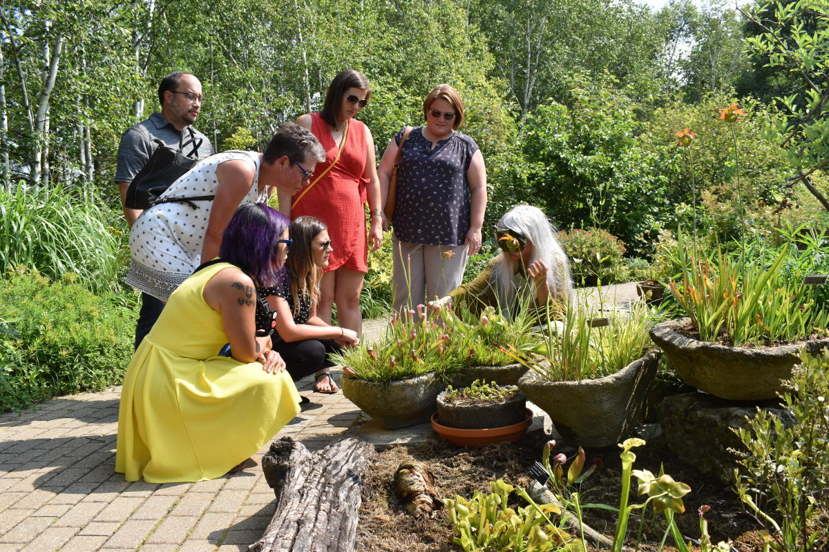 Visitors gathered around a plant outside at Olbrich Botanical Gardens