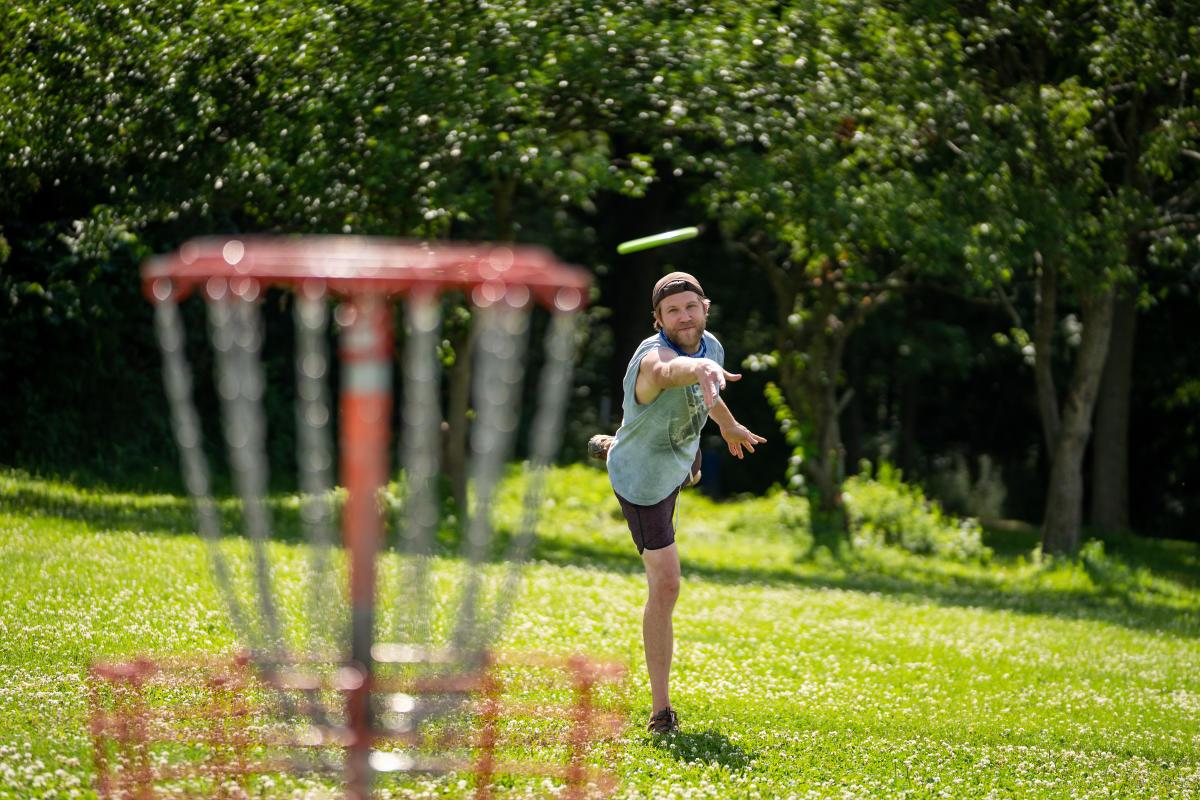 A man takes aim at a disc golf basket at Elver Park
