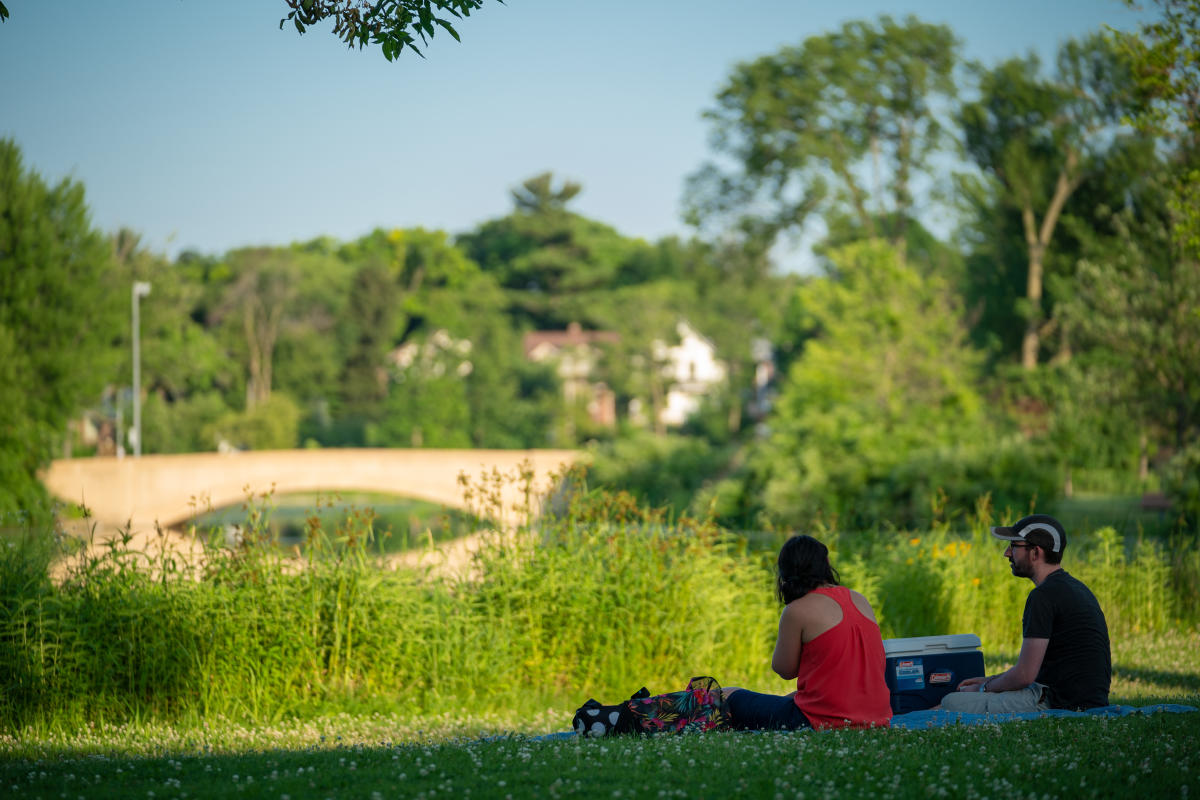A couple sits in a grassy area, enjoying the outdoors