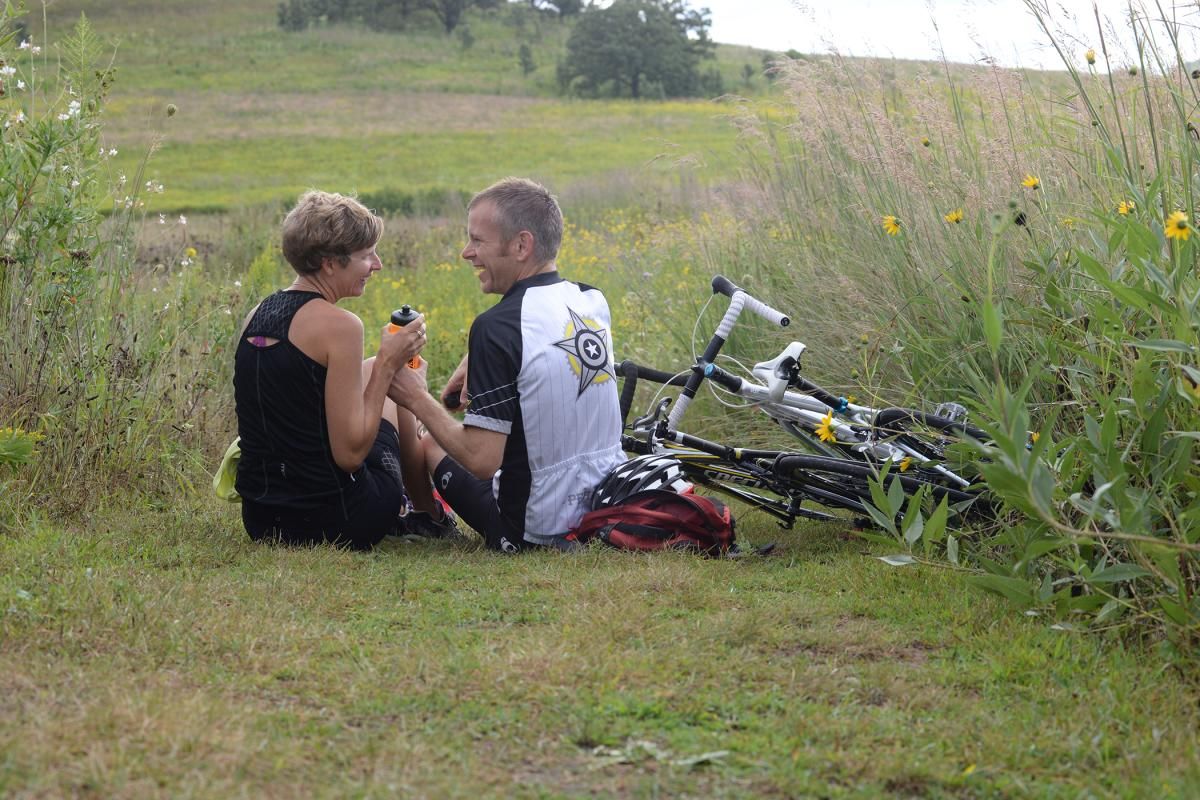 A couple taking a break from biking to have a picnic