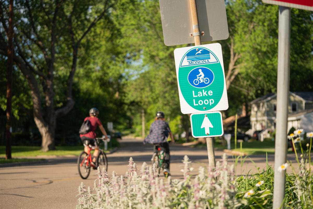 Bicyclists ride past a Lake Monona loop sign