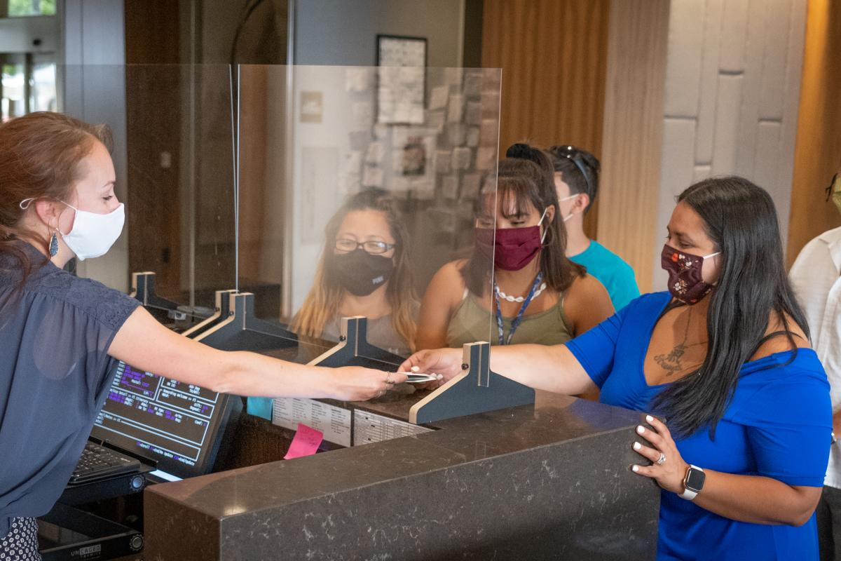 Guests wearing masks check in at a hotel