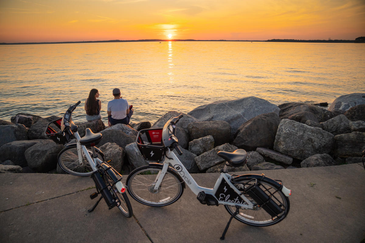 A couple takes a break from biking to watch a sunset