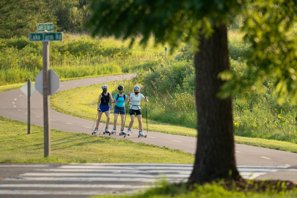 Three people roller ski on the Lower Yahara River Trail