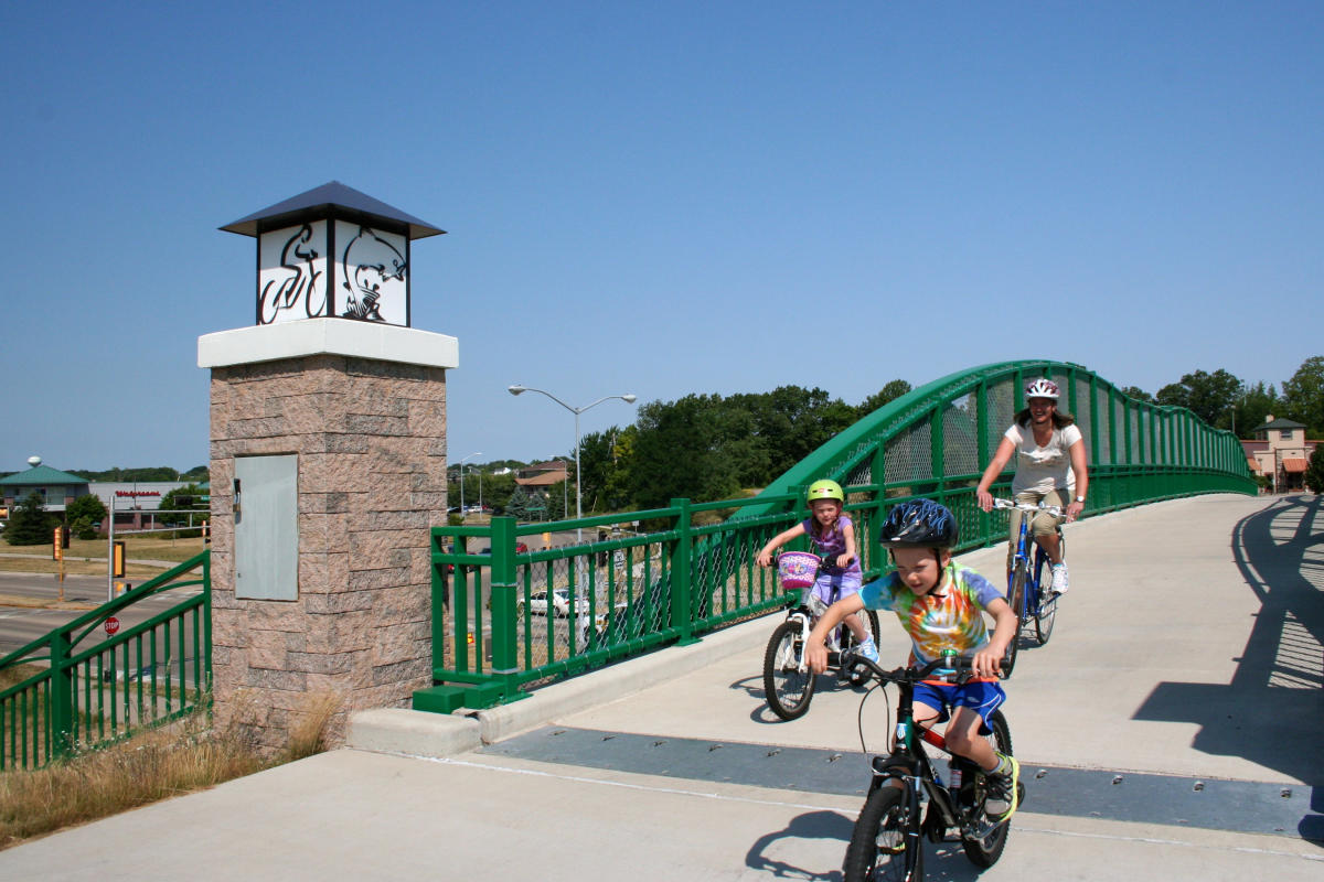 A woman and a little boy and girl bike over a bridge in Fitchburg