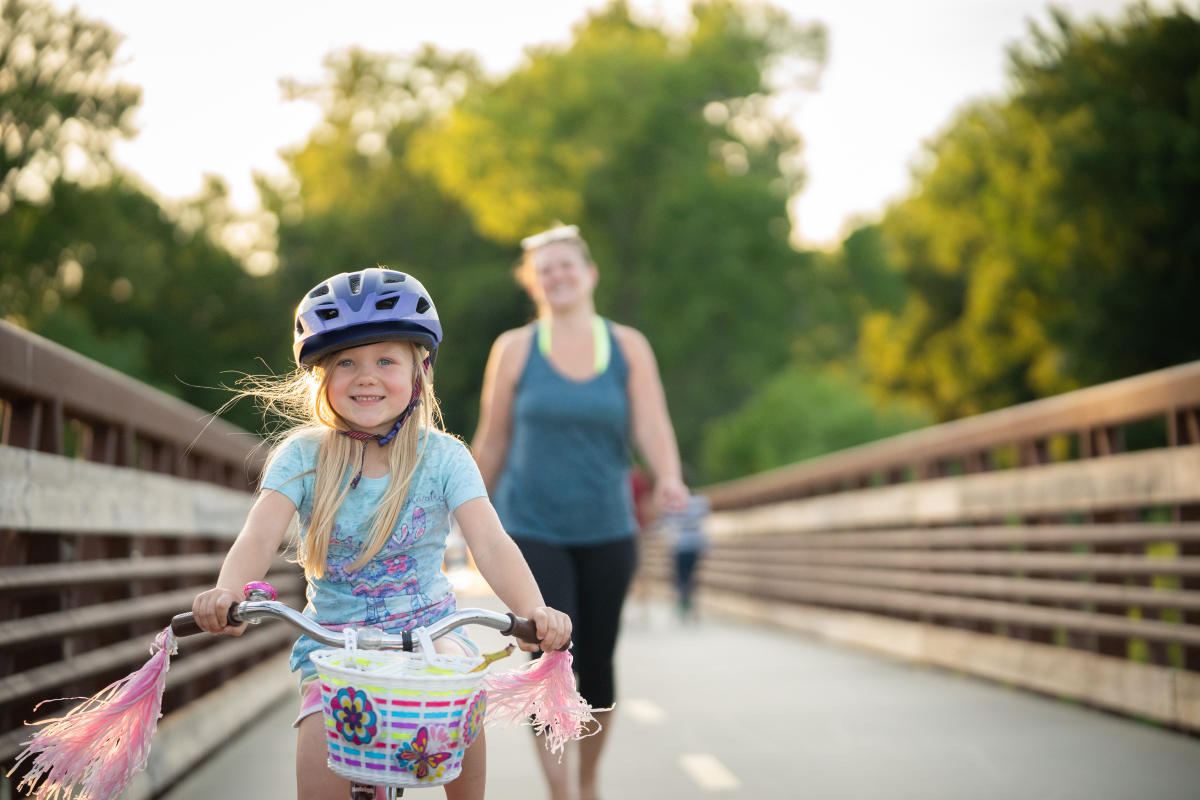 A girl rides her bike over the Lower Yahara River Trail bridge