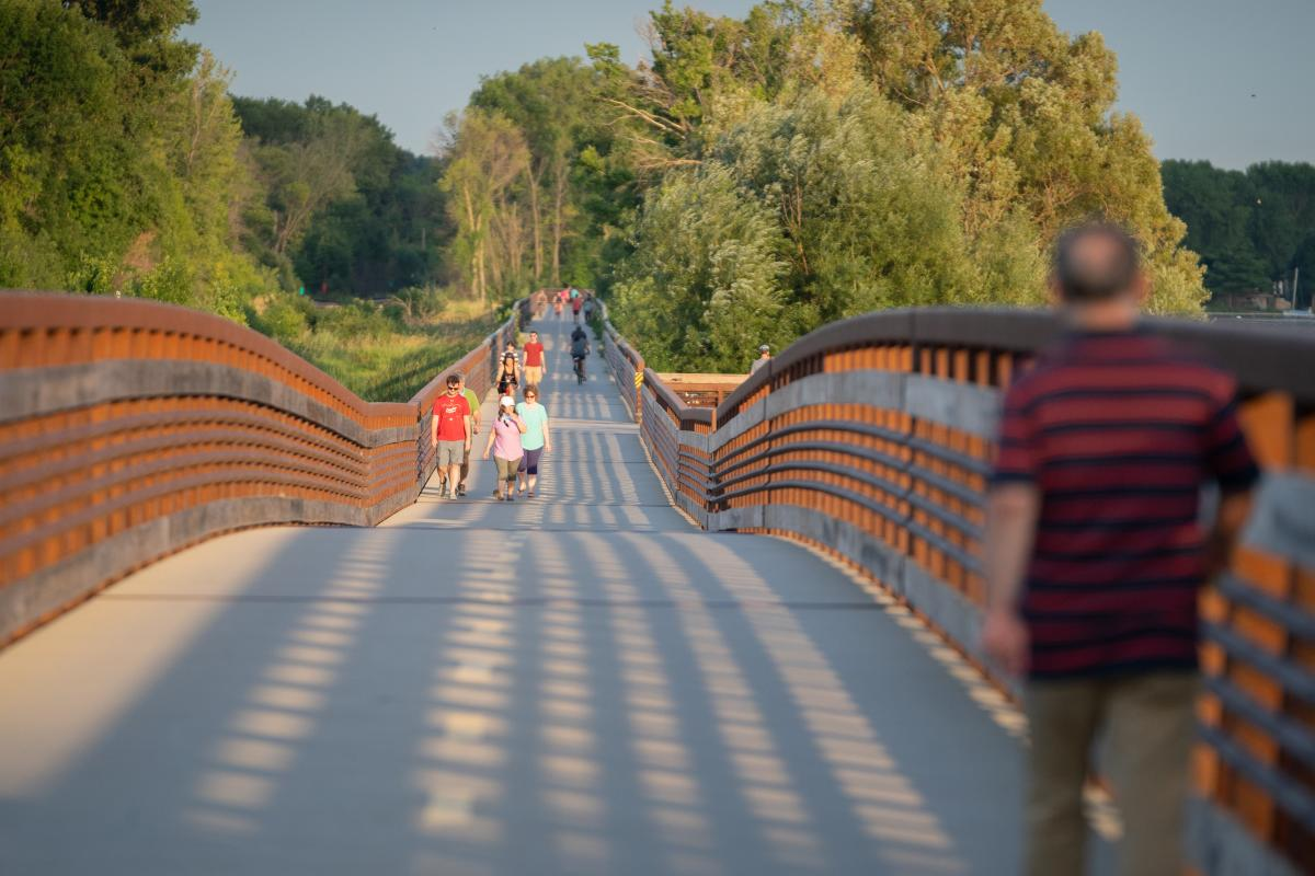 People walk the Lower Yahara River Trail bridge over Lake Waubesa