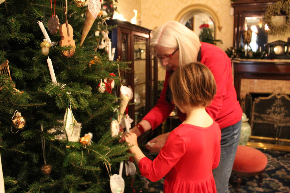 A woman and a young girl decorate a Christmas tree at Dalnavert Museum
