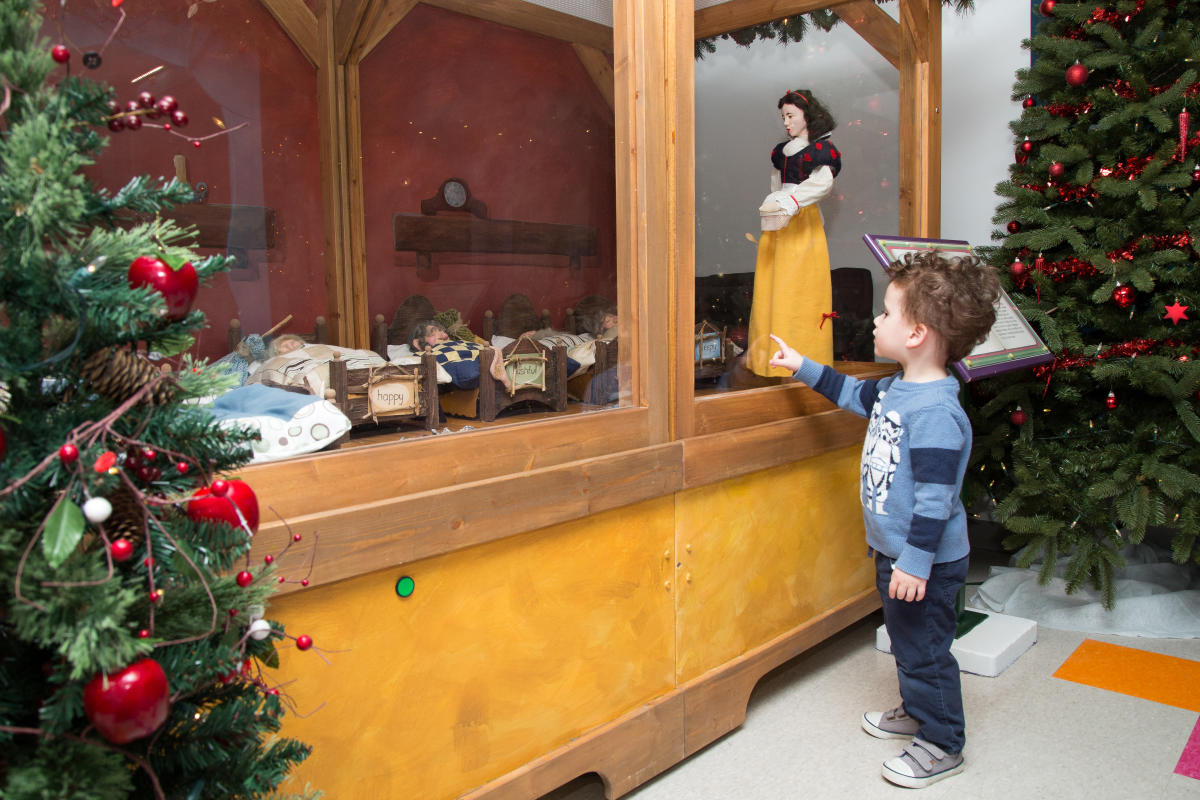 A young boy stands in front of the Snow White Eaton's Fairytale Vignette at the Manitoba Children's Museum