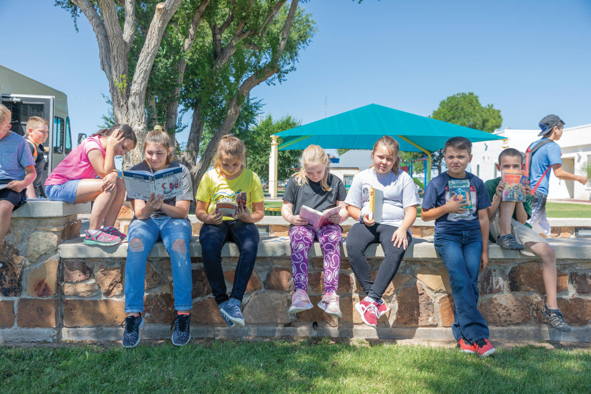 Elementary students showing off their bookmobile treasures.