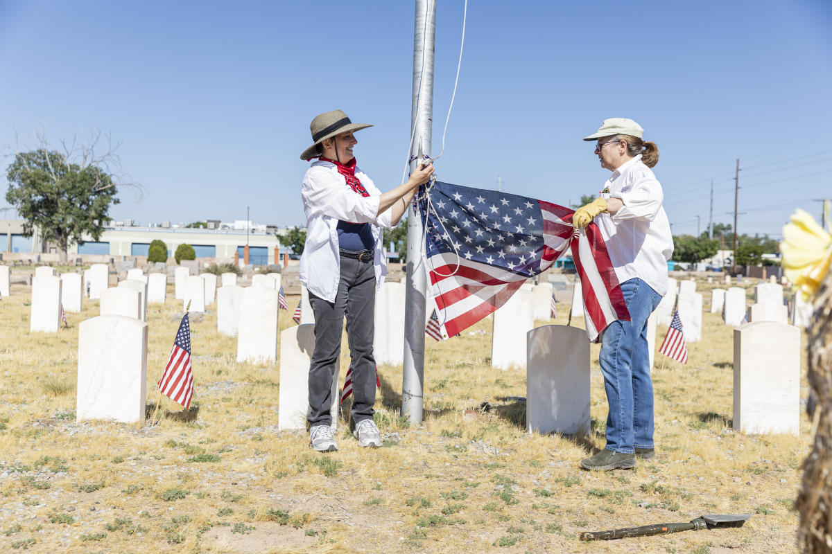 Gail Rubin (left), president of the Historic Fairview Cemetery Board, prepares to hoist a new flag at Fairview Memorial Park, Albuquerque