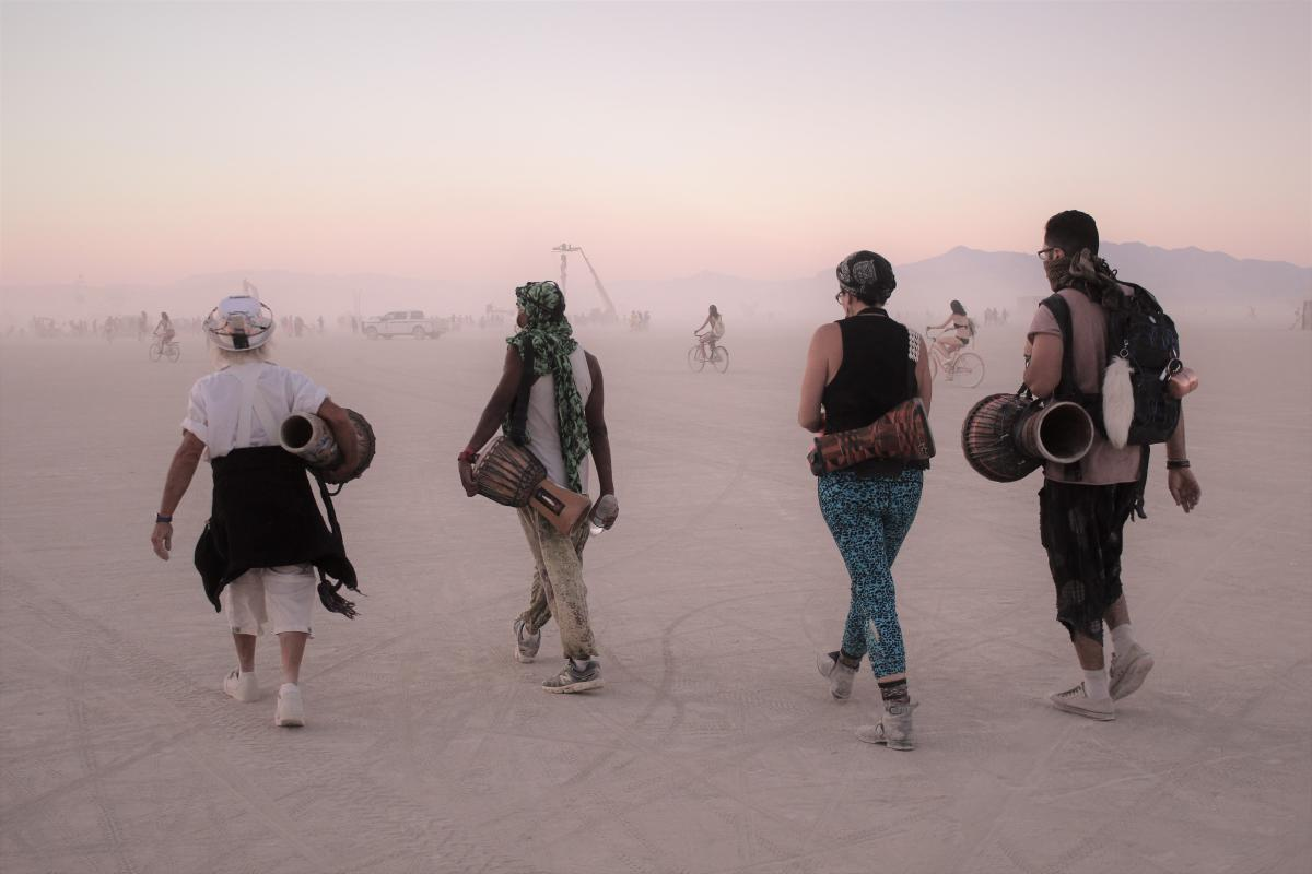 Four people walking across the dusty playa of Burning Man toward Black Rock City