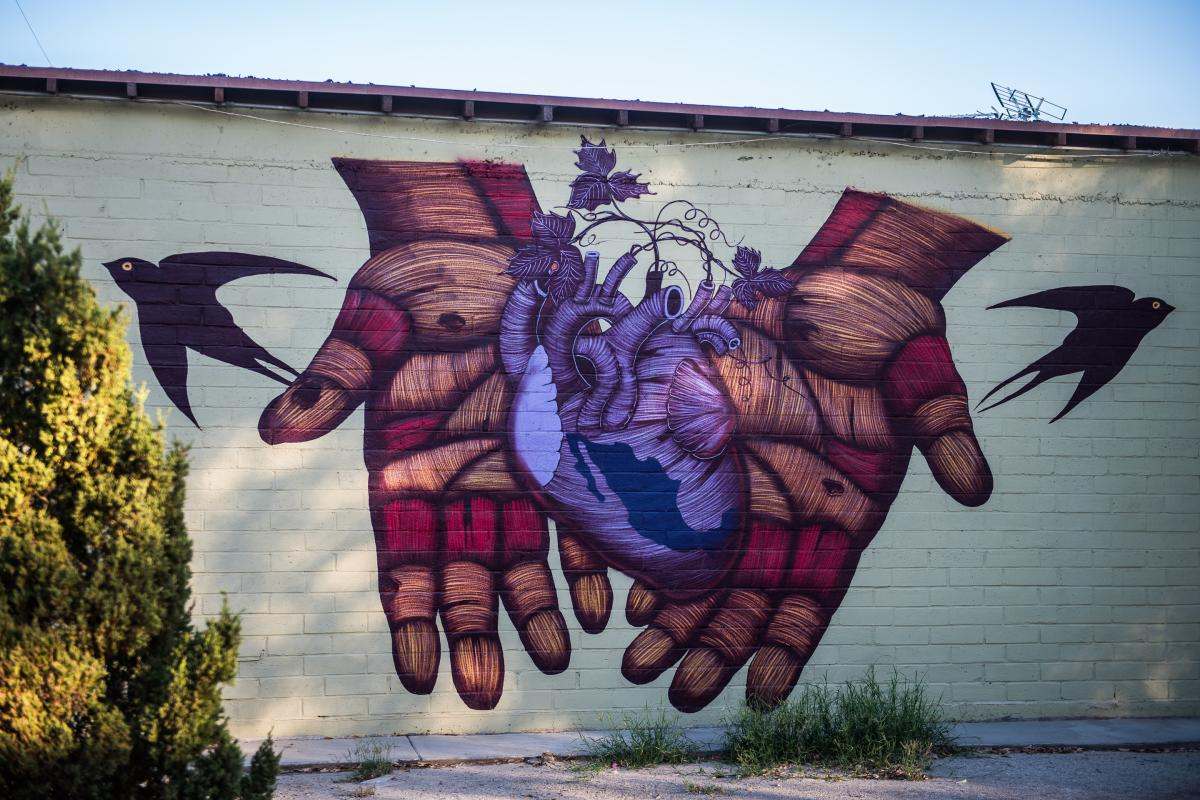 Mural of two hands holding a purple heart