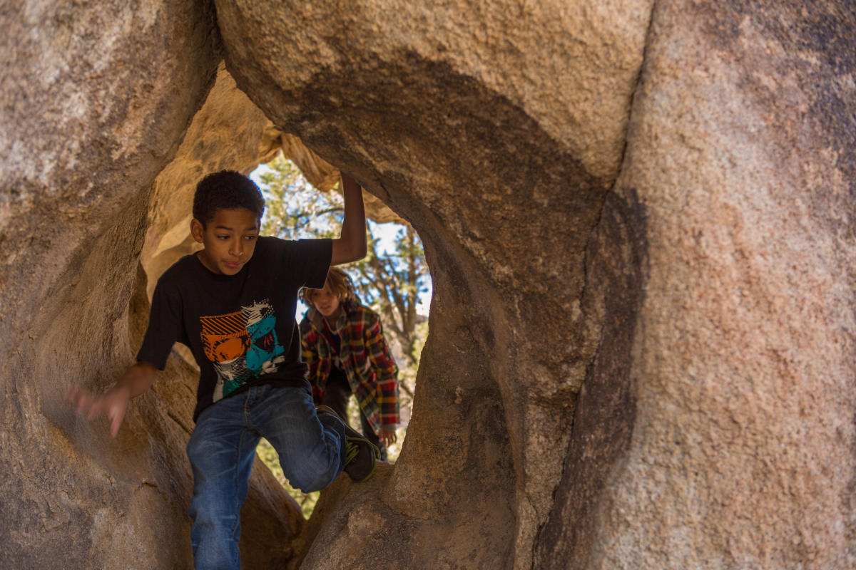 Youth hike through a rock formation during a Desert Adventures Tours outing.