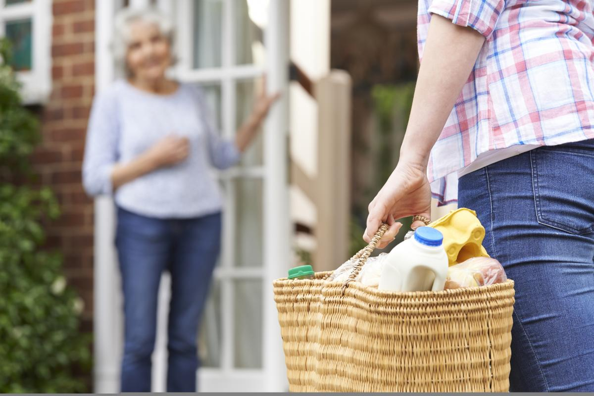 Woman receiving groceries that are being delivered