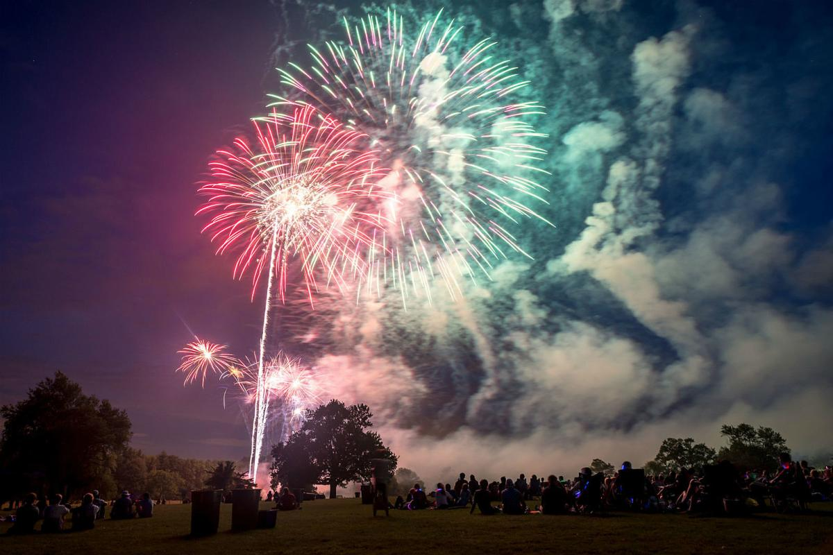 Colorful fireworks surrounded by smoke explode above trees as people watch from the ground