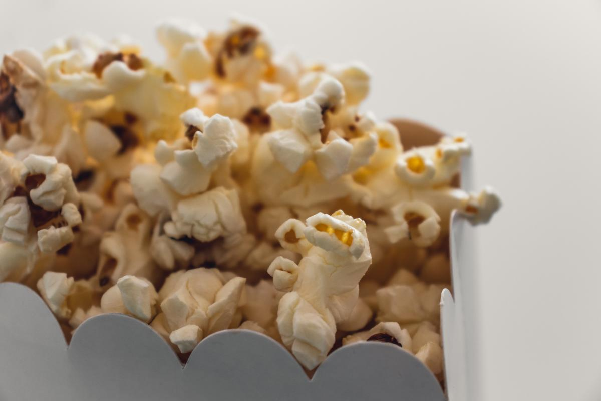 A white cardboard container filled with popcorn.