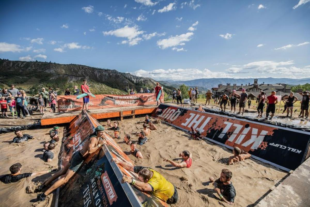 Tough Mudder Classic participants navigating through mud pit obstacle