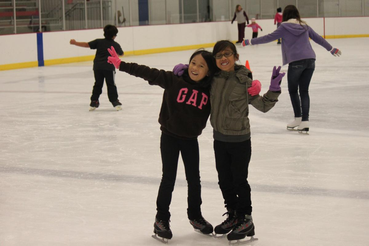 Two girls hugging and holding up peace signs at an ice skating rink