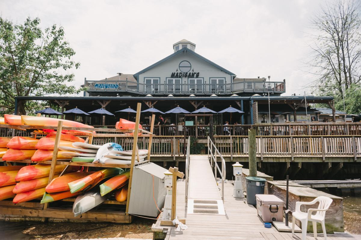 restaurant on the water with kayaks on the pier in front of the building