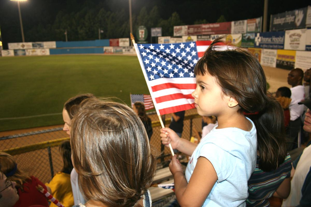 a girl holding a small flag at a baseball game