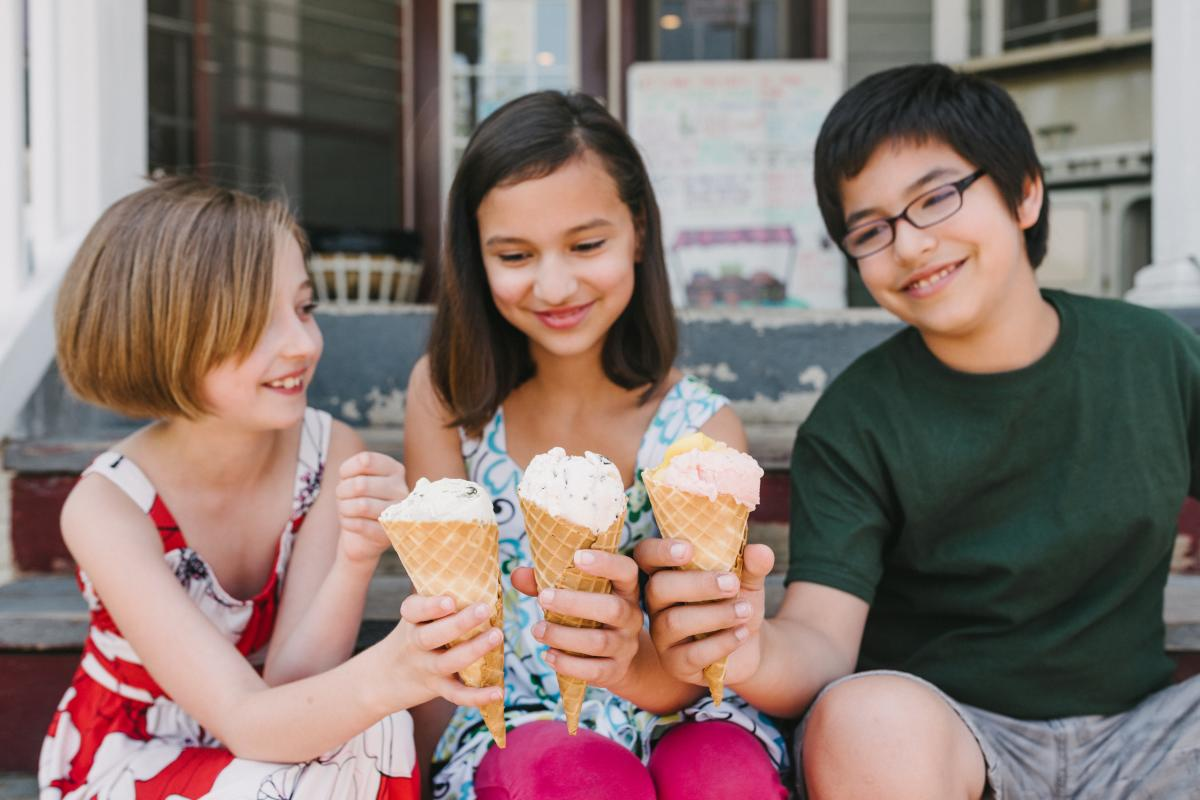 Three children holding ice cream in cones