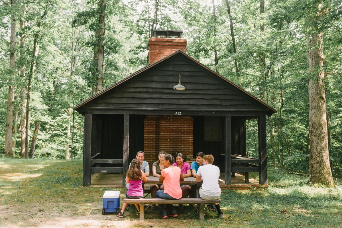 7 people sitting at a picnic bench in front of a cabin in a forest