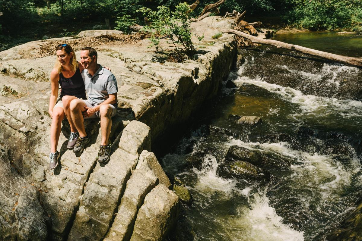 a couple sitting on the edge of a rock near water