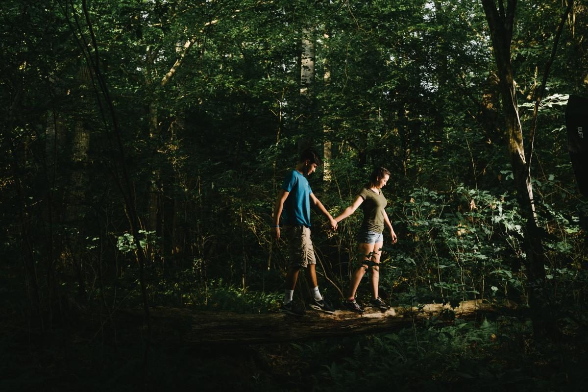 A young man and young woman walking on a log, holding hands in the forest