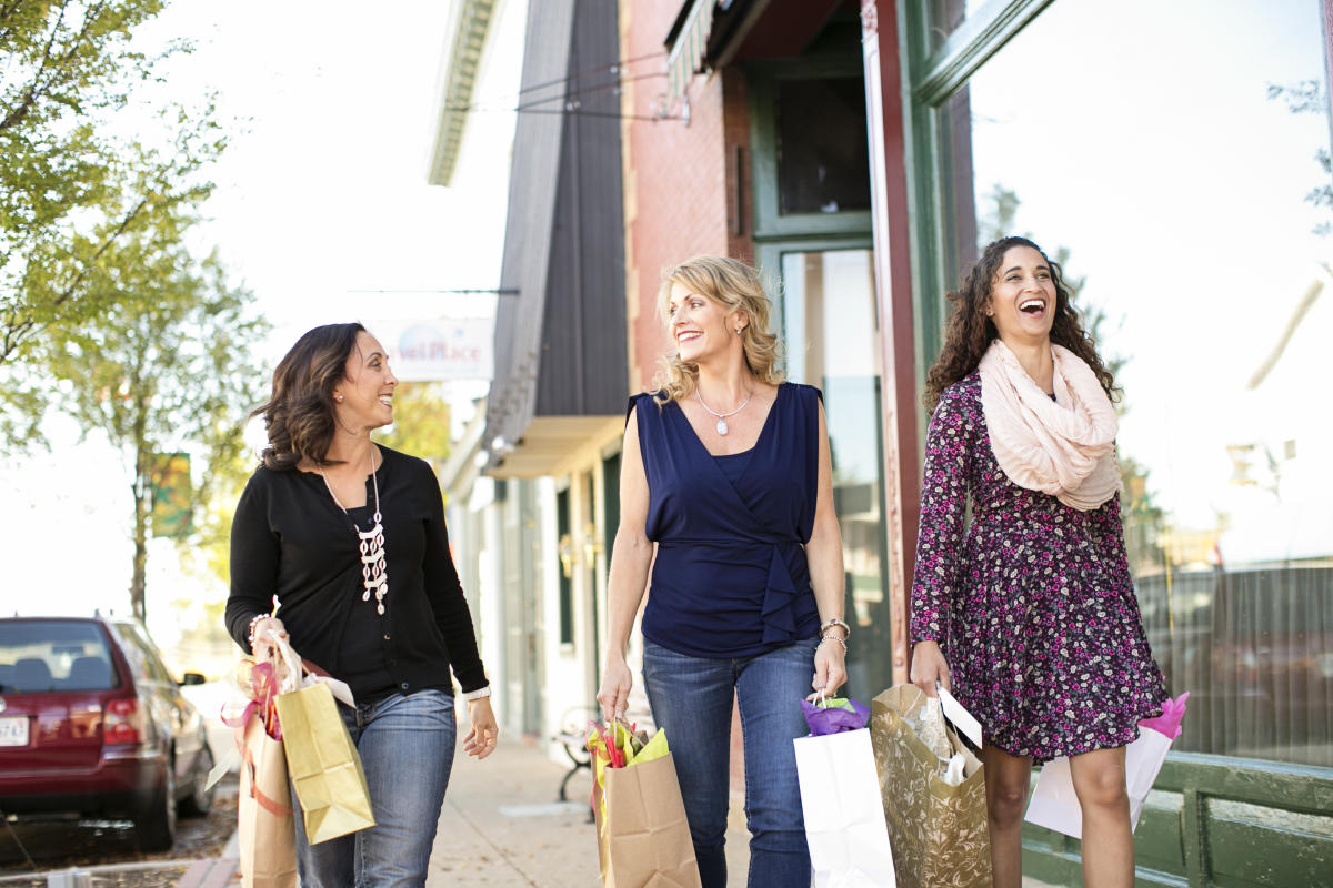 Three women holding shopping bags and walking in front of storefronts on a sidewalk.