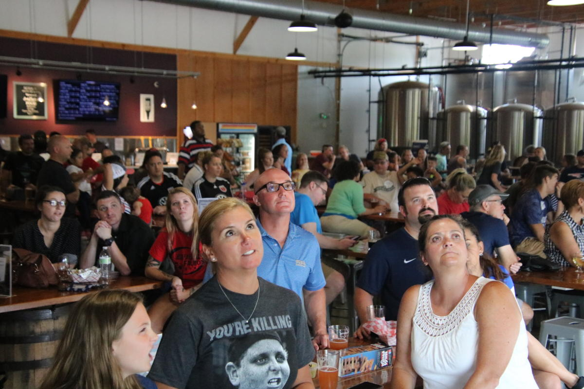 A large group of people visiting and enjoying a beer at The Farm Brewery at Broad Run