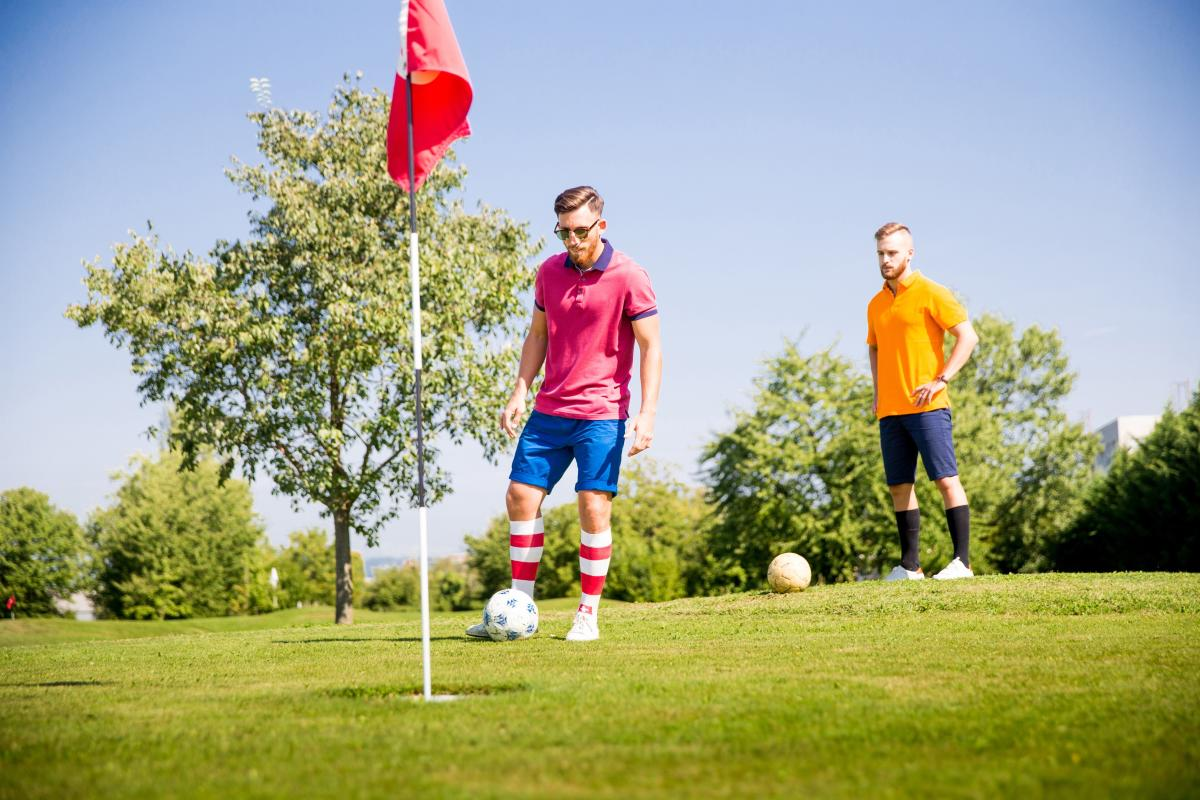2 men playing footgolf