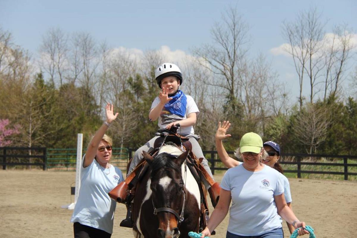 Child on horse at therapeutic riding center with volunteers on each side