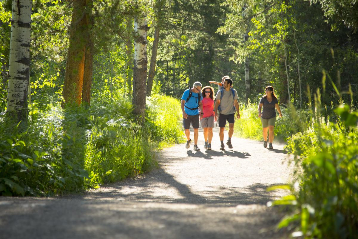 A family enjoys a hike along the Spring Creek Trail